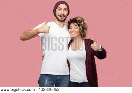 Awesome. Portrait Of Positive Couple Of Friends In Casual Style Standing, Hugging And Showing Thumbs
