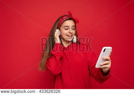 Photo Of Beautiful Positive Smiling Brunette Girl Wearing Red Hoodie Isolated On Red Background Hold