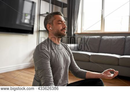 Calm Middle-aged Caucasian Man In Headphones Listen To Mantras Meditate Practice Yoga At Home. Mindf
