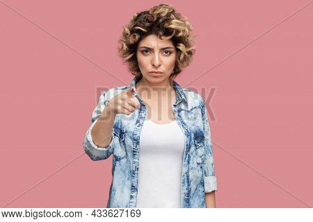 Hey You. Portrait Of Serious Young Woman With Curly Hairstyle In Casual Blue Shirt Standing, Looking
