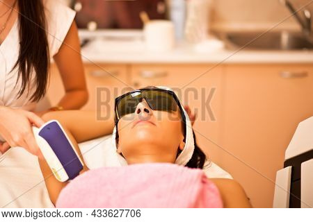Laser Hair Removal On Woman Underarm. Female Having Laser Hair Removal Treatment In Salon.