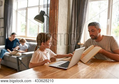 Caring Caucasian Young Father Do Homework With Small Teen Daughter Study Online On Computer At Home.