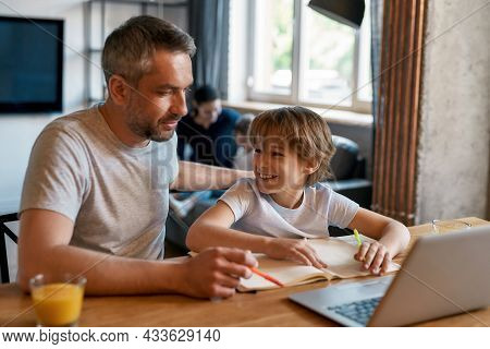 Smiling Excited Boy Child Enjoy Studying Online On Computer With Caucasian Father. Caring Dad Help S