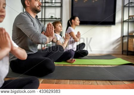 Close Up Crop Of Calm Caucasian Young Family With Children Hold Mudra Hands Meditate At Home Togethe