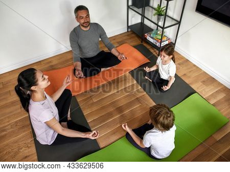 Top Down View Of Calm Parents With Teen Kids Practice Yoga Meditate With Mudra Hands With Eyes Close