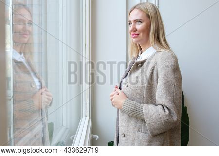 Elegant Blonde Woman Stands In Front Of Her Reflection In The Window And Smiles. Woman In An Autumn