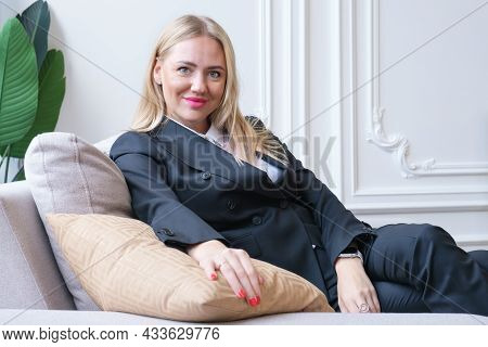 Attractive Blonde Woman In A Business Gray Suit Is Sitting On The Couch. The Woman Smiles And Looks