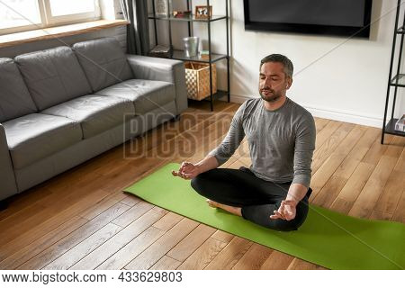 Calm Middle-aged Caucasian Man In Earphones Sit In Lotus Pose With Mudra Hands Meditate At Home. Min