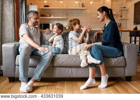 Overjoyed Young Caucasian Family With Teen Kids Relax On Sofa At Home Have Fun Talking Chatting. Hap