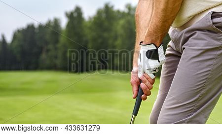 Hands of a playing man holding a golf club on the field