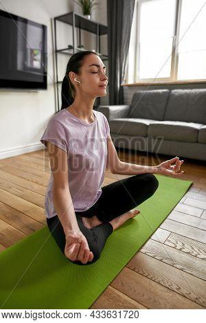 Vertical Narrow Shot Of Young Caucasian Woman In Sportswear Headphones Meditate Practice Yoga At Hom