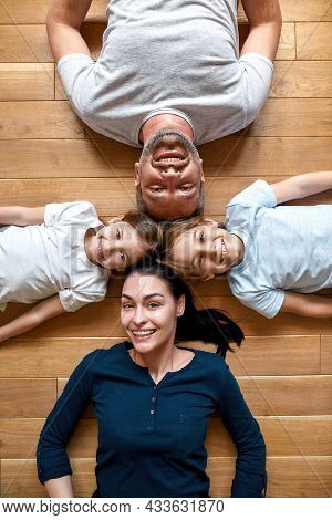 Vertical Narrow Shot Portrait Of Happy Young Caucasian Family With Small Teen Children Lying On Floo