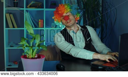 Young Man In Image Of Clown With Closed Eyes Typing On Keyboard. Funny Clown Sits In Armchair Before
