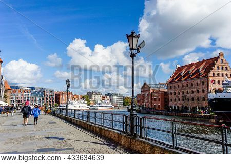 Tourists Enjoy A Visit To The Historic City Center Of Danzig Along The Boardwalk Of The Motlawa Rive