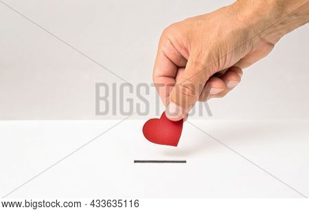 Red heart symbol is put by person's hand into slot of white donation box, Concept of donorship, life saving or charity
