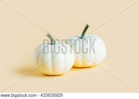 Ripe Pumpkins On A Yellow Pastel Background. Minimalistic Concept For Thanksgiving Card Or Backgroun