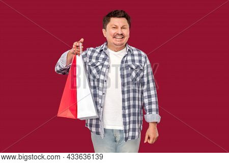 Happy Modern Funny Middle Aged Man In White T-shirt And Checkered Shirt Standing And Holding Shoppin