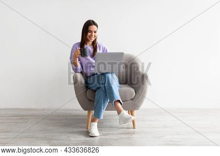 Positive Caucasian Woman Working Online, Sitting In Armchair With Coffee And Using Laptop Against Wh