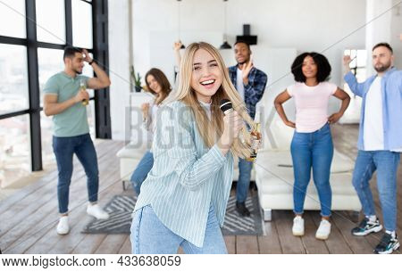 Cheerful Young Blonde Lady With Bottle Of Beer And Microphone Singing Karaoke With Diverse Friends A