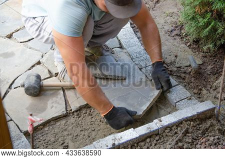 Construction Of Pavement Near The House. Bricklayer Places Concrete Paving Stone Blocks For Building