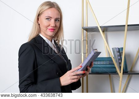 Attractive Blonde Business Woman In Business Suit Stands At Bookshelf And Chooses A Book To Read