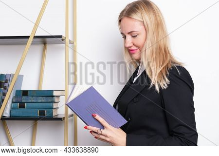 Attractive Blonde Business Woman In A Business Suit Stands At The Bookshelf And Reads A Book