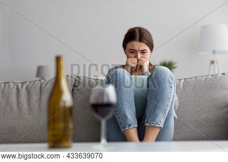 Sad Crying Despaired European Young Lady Suffering From Stress, Grief And Difficulties With Bottle A