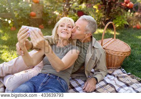 Happy Senior Couple Taking Selfie On Smartphone, Having Picnic And Resting In Garden Outside, Enjoyi