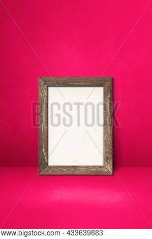 Wooden Picture Frame Leaning On A Pink Wall. Blank Mockup Template