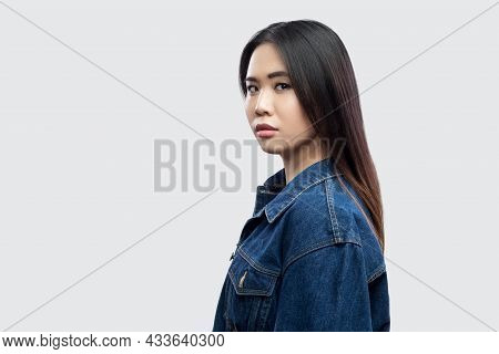 Profile Side View Portrait Of Calm Serious Beautiful Brunette Asian Young Woman In Casual Blue Denim