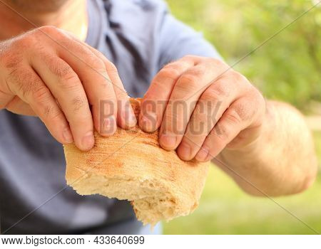 The Man Breaks Off The Pita Bread With His Hands. Street Food In The Hands Of A Man. The Cook Prepar