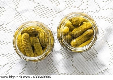 Small pickles. Marinated pickled cucumbers in jar on kitchen table. Top view.