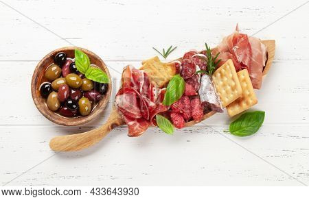 Antipasto board with prosciutto, salami, crackers, cheese and olives. Top view flat lay