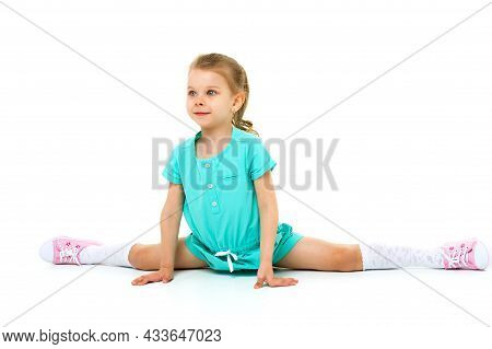 Adorable Active Little Girl Doing Split On Floor. Adorable Girl Dressed In Cotton Jumpsuit, White Kn