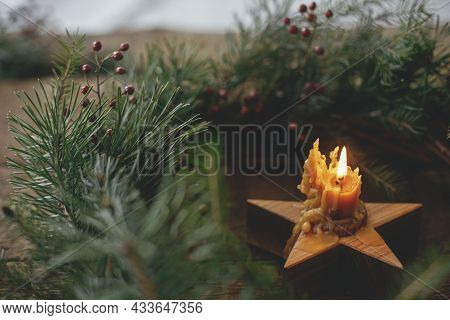Christmas Advent. Stylish Rustic Burning Candle In Christmas Wreath On Old Wooden Background. Moody