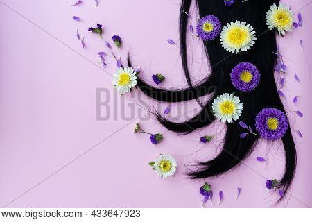 Black Hair With Yellow And Lilac Flowers And Petals On It. Hair Care Concept.