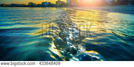 Wavy curves  of  sea is covered  in golden sunset light. Sea at sunset sunlight. Wavy curves pattern on beach.   Waves in bokeh focud
