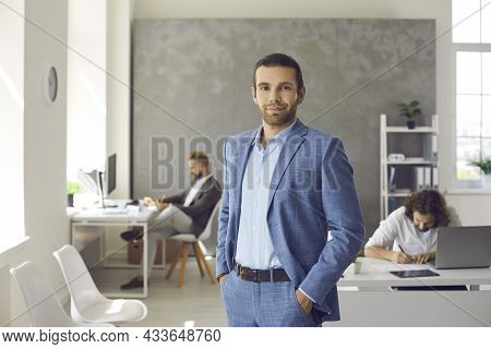 Portrait Of Successful Businessman In Suit In Office