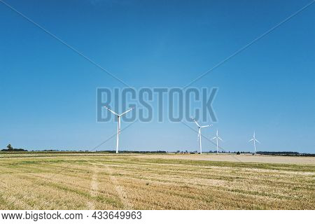 Windmill Among Agricultural Fields. Wind Turbine Generator At Summer Day. Wind Energy Concept. Suist