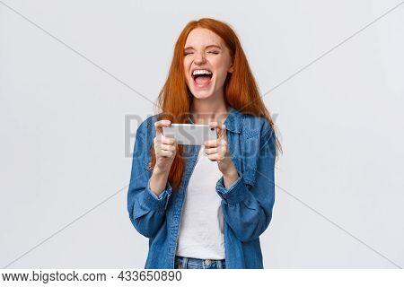 Carefree Good-looking Millennial Redhead Girl Having Fun, Watching Favorite Vlogger, Laughing Over H