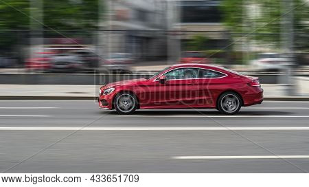 Mercedes-benz C205 Coupe Rides On City Road. Side View Of Red Mercedes C-class Car On Asphalt Road I
