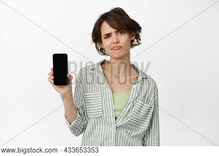 Disappointed Frowning Woman Showing Mobile Phone Screen, Sulking About Something On Smartphone, Comp