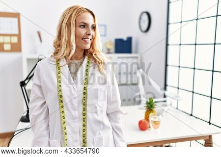 Beautiful blonde nutritionist woman at dietitian clinic looking away to side with smile on face, natural expression. laughing confident.