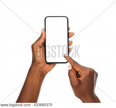 Close up hands of woman showing smartphone against white background. African woman hands touching blank screen of cellphone over white wall. Close up hands using app on mobile phone.