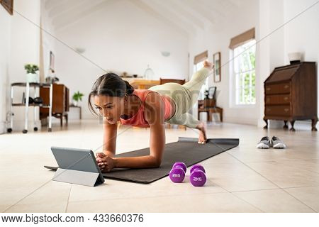 Mid adult fitness woman exercising at home and watching training videos on digital tablet. African american fit woman doing planks with a leg outstretched during online workout.