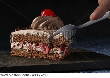 Fork Cutting Portion Of Chocolate Cake And Cherries