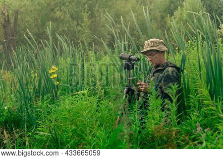 Man Birdwatcher Records The Results Of The Observations While Standing Among The Tall Grass In The W
