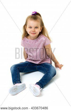 Cute Little Blonde Girl Sitting On The Floor. Portrait Of Attractive Blonde Gray Eyed Preschool Girl