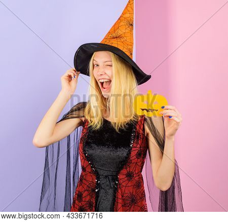 Smiling Witch With Paper Carved Pumpkin. Winking Girl In Witches Hat And Halloween Costume. Carving