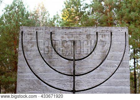 Defocus Menorah Symbol On Concrete Concrete Slab In Forest And Nature. Symbols Of Jewish People. Mem